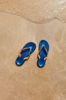 Blue flip flops on the sand with water approaching