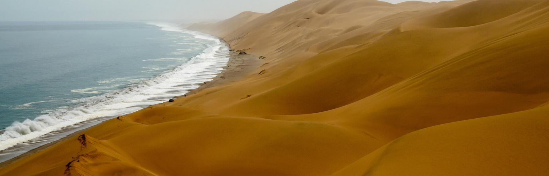 A view of desert dunes where they meet the ocean.
