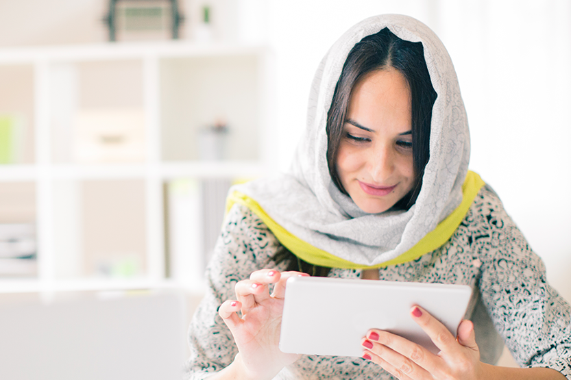 Woman wearing a scarf over her head reading an ipad