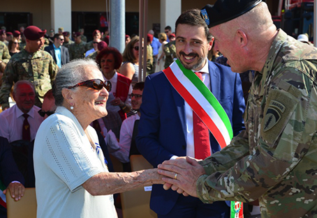 Elderly lady shaking hand of military personnel