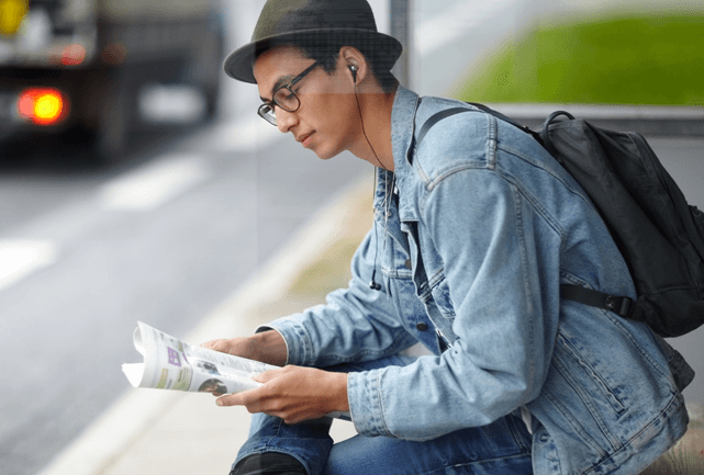 Young man in a hat, sitting at bus stop reading a newspaper.