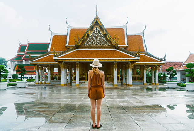 Tourist Woman standing infront of the Wat Ratchanatdaram in Bangkok.