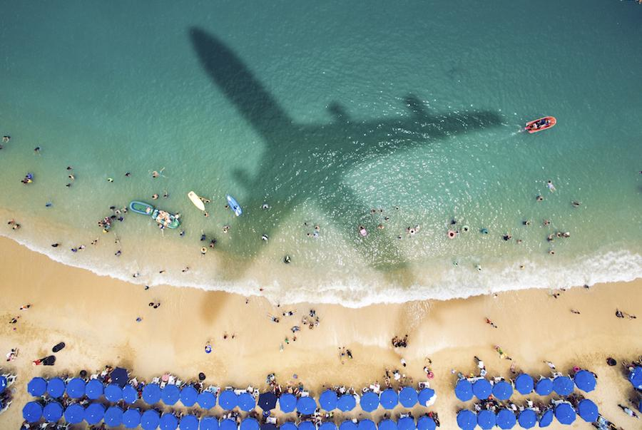 Shadow of an airplane over a crowded beach