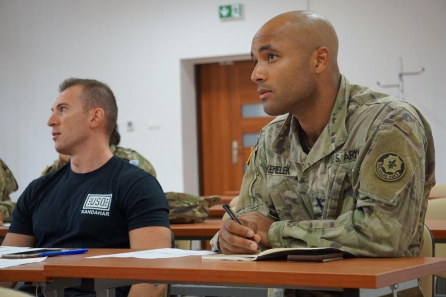 Two soldiers listen to a Polish linguist as she teaches grammar rules during a Polish language class.