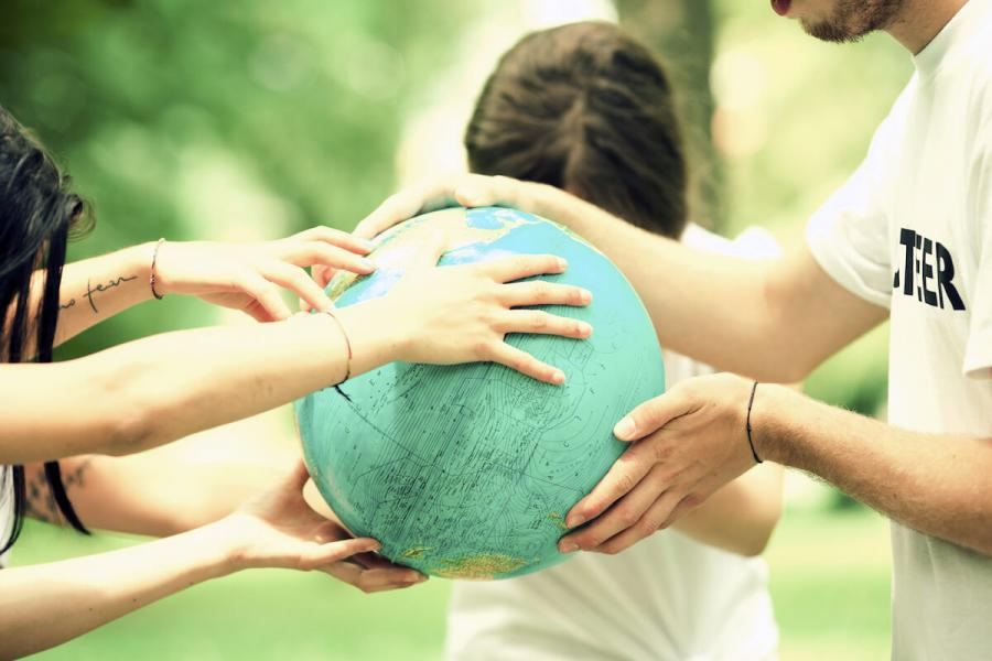 A group of hands reaching out to hold a globe.