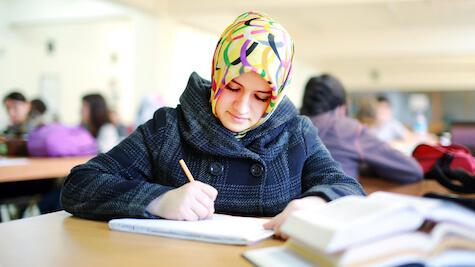 A Middle-Eastern young woman writing notes down in a classroom.