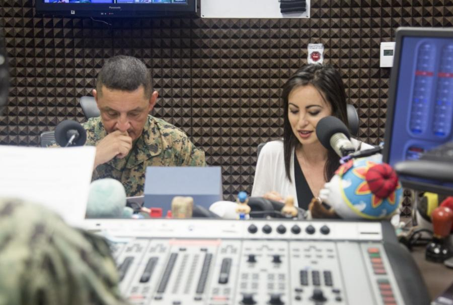 Mari Gregory and Sgt. Maj. Mario Marquez sit in a recording studio as they speak on their radio show.