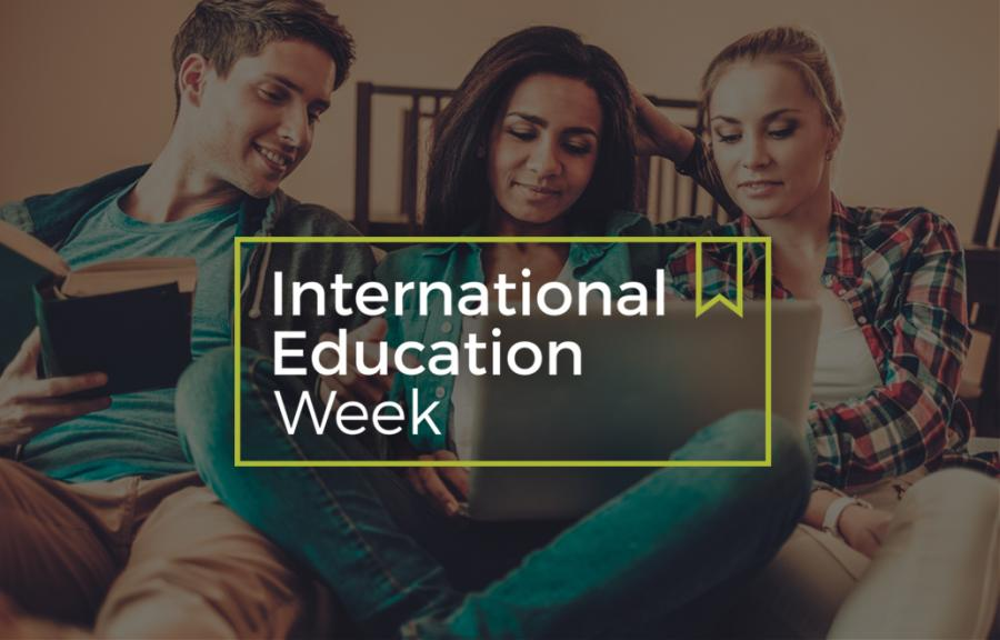 "Three people sitting together looking at a person's laptop, with a banner saying ""International Education Week"" over top"