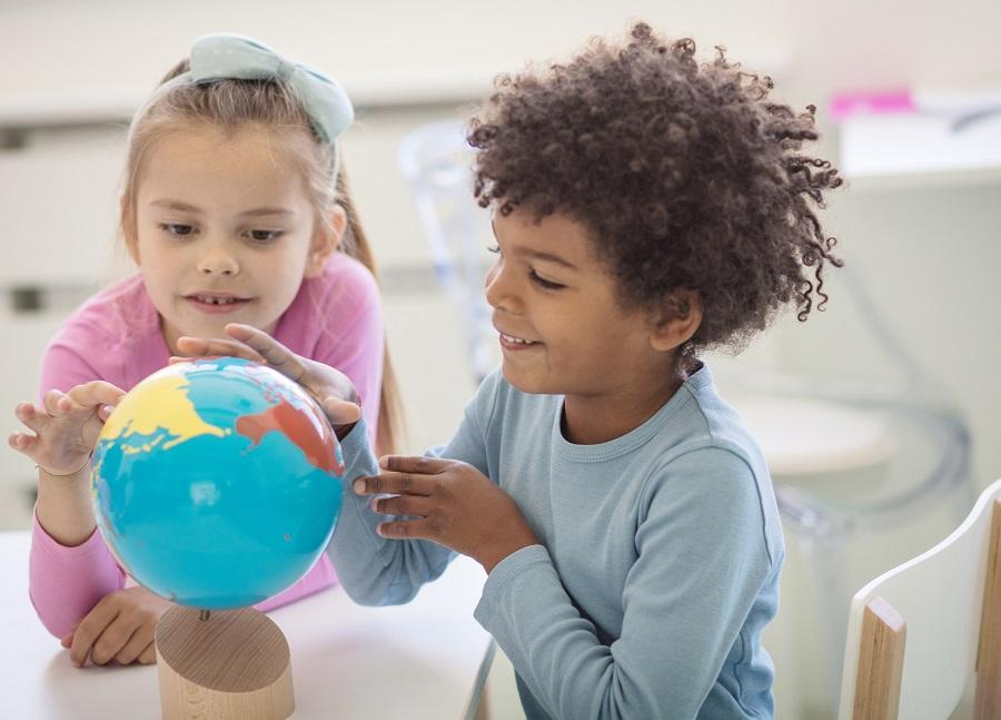 Two children sitting at a table, looking at a small globe.