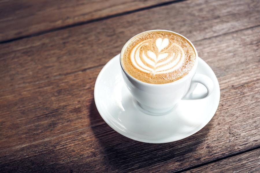 Close up of a hot cappuccino in a white coffee cup with heart shape latte art on dark brown old wood table at a cafe.
