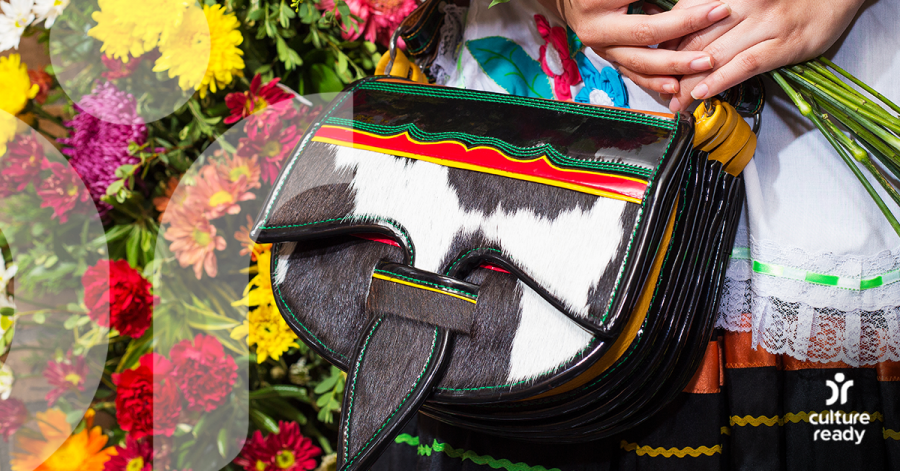 Close-up image of a purse being held by a woman, with flowers in the background