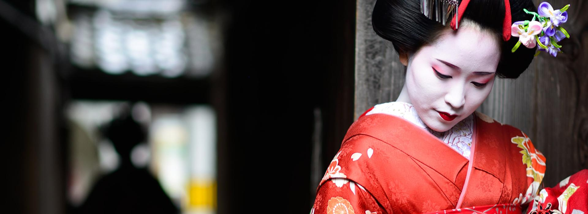 Geisha looking down in red kimono