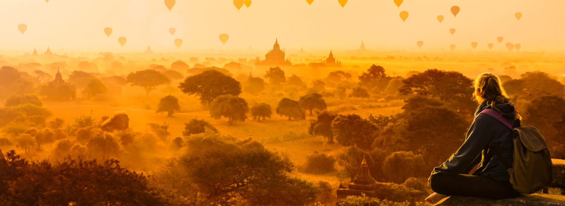 A woman sitting on ruins in Myanmar, looking out at a yellow-red sky full of hot air balloons.
