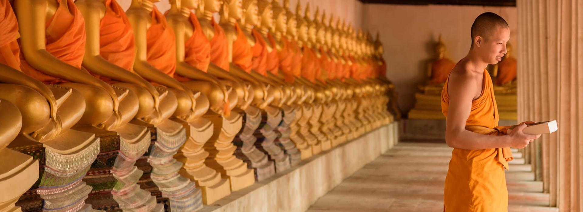 A monk in orange robes standing in front of a line of statues in a temple.