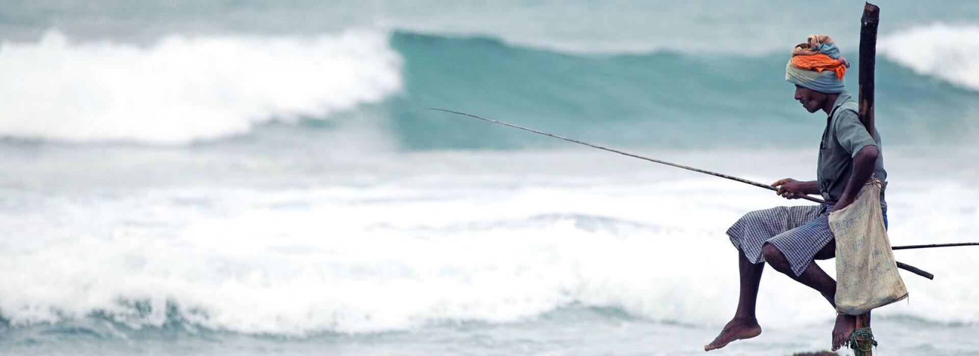 Sri Lankan Fisherman sitting on a pole fishing near ocean shore.