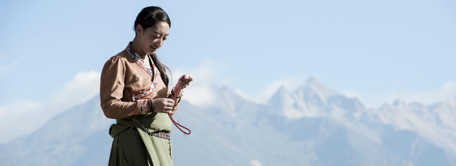 Girl on field near mountains holding a traditional necklace in her hands.