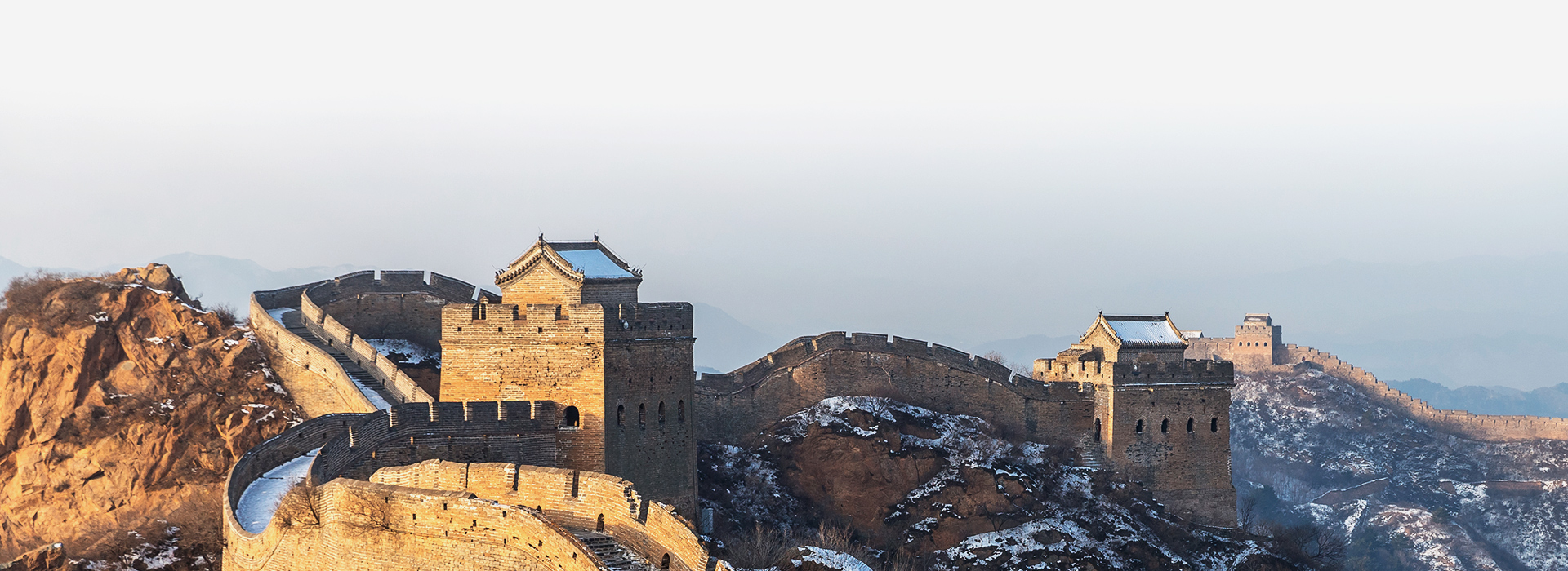 A portion of China's Great Wall cuts across a mountainous, snow-covered landscape.
